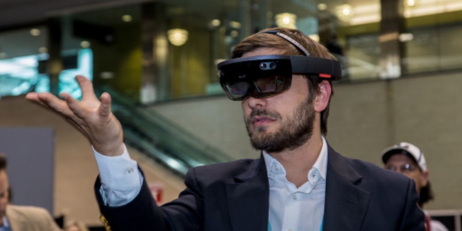A man holds virtual object while wearing augmented reality glasses.