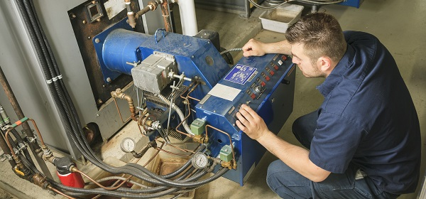 A technician inspects a commercial boiler.