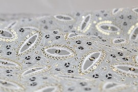 The embroidery systems from LÄSSER manufacture complex nitrogen compounds - also here with sequins and laser-cut perforations.