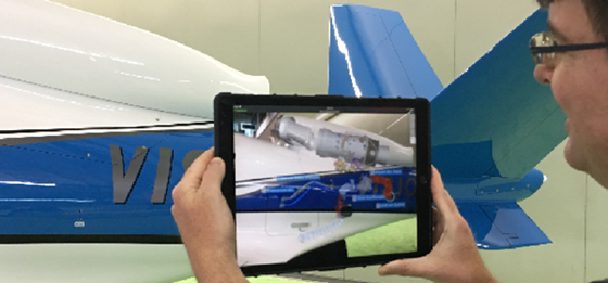 Man reviews digital model in context of physical airplane using AR